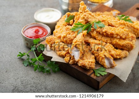 Breaded chicken strips with two kinds of sauces on a wooden Board. Fast food on dark brown background #1214906179
