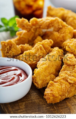 Breaded chicken tenders with ketchup, salad and soda