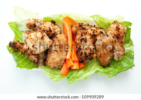 breaded chicken wings with carrot sticks on a bed of lettuce