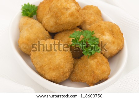 Breaded deep fried mushrooms garnished with parsley. Party food table set up shot from above.