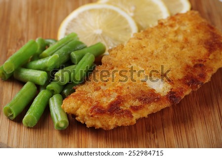 Breaded fried fillet and potatoes with asparagus and sliced lemon