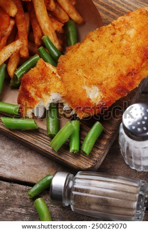 Breaded fried fish fillet and potatoes in paper bag with asparagus on cutting board and rustic wooden background