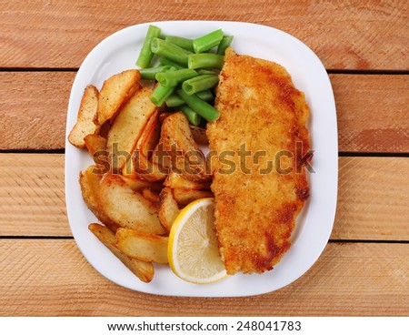 Breaded fried fish fillet and potatoes with asparagus and sliced lemon on plate and wooden planks background
