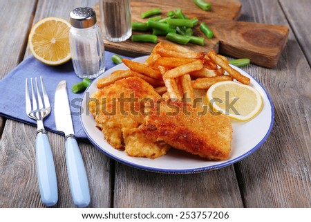Breaded fried fish fillets and potatoes with asparagus and sliced lemon on plate and wooden planks background