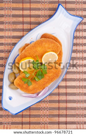 Breaded hake fillets in the fish-shape plate - aerial view