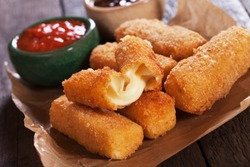 Breaded mozzarella cheese sticks with ketchup and bbq sauce