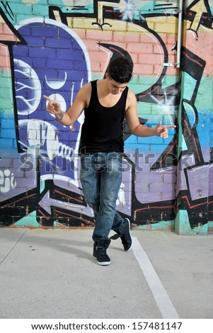 break-dance dancer on a city street posing with a dance move