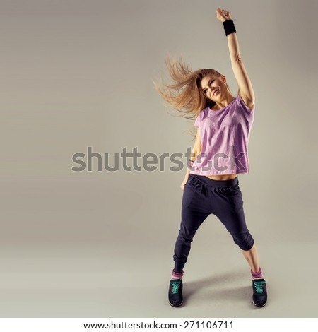 Break dance party. Stylish smiling fit woman dancing on studio background. Sport and recreation concept.
