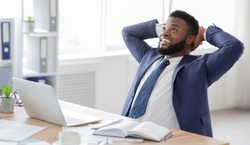 Break in work. Young african businessman in formalwear relaxing at workplace, free space