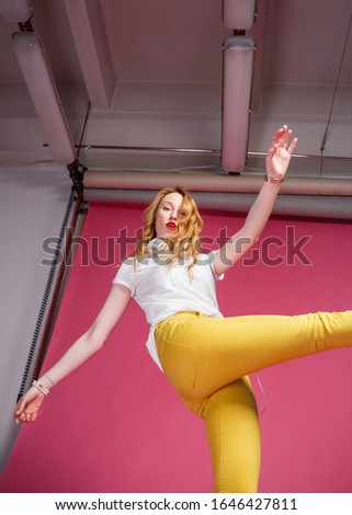 Break the rules. Attractive leggy blonde in yellow jeans poses in the studio on a pink background. Kick motion. Lower view.