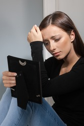 Break-up. Depressed young women holding a photo frame and crying