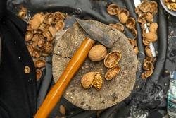 break walnuts with hammer on wood