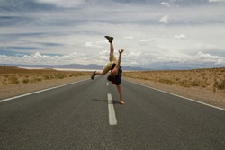 Breakdance. Recreational. Young caucasian man handstand and twirl in the asphalt desert road.