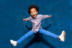 Breakdancing joyful african american cute little child boy levitating in jump. Funny small excited dancing kid having fun hop. Positive emotions and triumph concept.