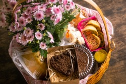 Breakfast basket with chocolate, quiches and flowers on a wooden table