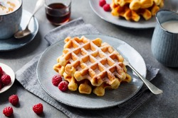 Breakfast Belgian waffles with maple syrup and fresh raspberry. Grey background.