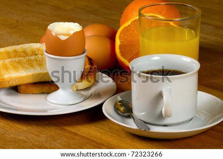 Breakfast: Boiled egg, toast, coffee and fresh orange juice. On Wooden table