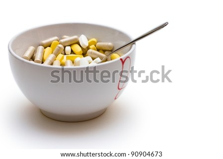 Breakfast bowl full of brown, yellow and white pills, concept for medical / healthcare. Shallow depth-of-field image. Isolated over white background.