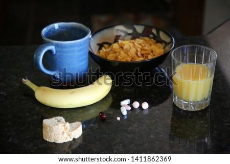 Breakfast cereal. Breakfast with Cereal, Orange Juice, Milk, Vitamins, Raisins, Banana, and Coffee.  #1411862369