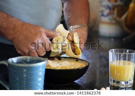 Breakfast cereal. Breakfast with Cereal, Orange Juice, Milk, Vitamins, Raisins, Banana, and Coffee.  #1411862378