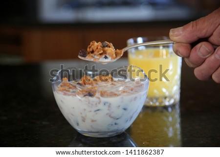 Breakfast cereal. Breakfast with Cereal, Orange Juice, Milk, Vitamins, Raisins, Banana, and Coffee.  #1411862387