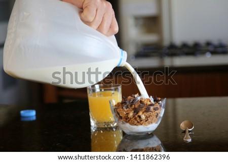 Breakfast cereal. Breakfast with Cereal, Orange Juice, Milk, Vitamins, Raisins, Banana, and Coffee.  #1411862396