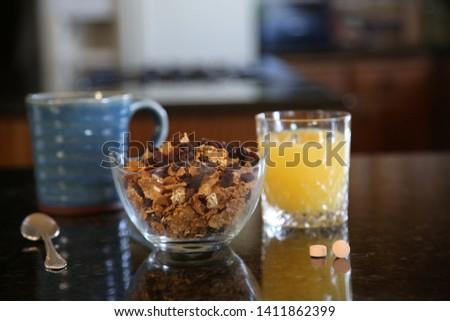 Breakfast cereal. Breakfast with Cereal, Orange Juice, Milk, Vitamins, Raisins, Banana, and Coffee.  #1411862399