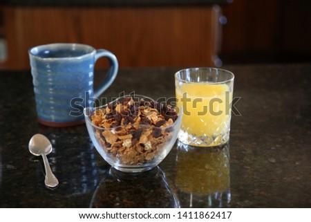 Breakfast cereal. Breakfast with Cereal, Orange Juice, Milk, Vitamins, Raisins, Banana, and Coffee.  #1411862417