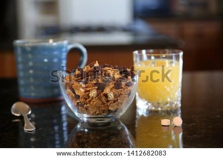 Breakfast cereal. Breakfast with Cereal, Orange Juice, Milk, Vitamins, Raisins, Banana, and Coffee.  #1412682083