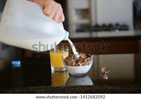 Breakfast cereal. Breakfast with Cereal, Orange Juice, Milk, Vitamins, Raisins, Banana, and Coffee.  #1412682092