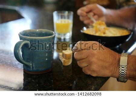 Breakfast cereal. Breakfast with Cereal, Orange Juice, Milk, Vitamins, Raisins, Banana, and Coffee.  #1412682098