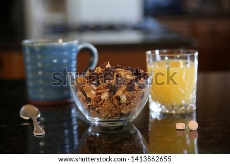 Breakfast cereal. Breakfast with Cereal, Orange Juice, Milk, Vitamins, Raisins, Banana, and Coffee.   #1413862655