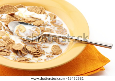 Breakfast cereal with milk and spoon in orange plate with napkin on white background.