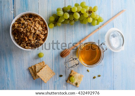 Breakfast cereals with grapes, honey and muesli on a blue background, top view #432492976