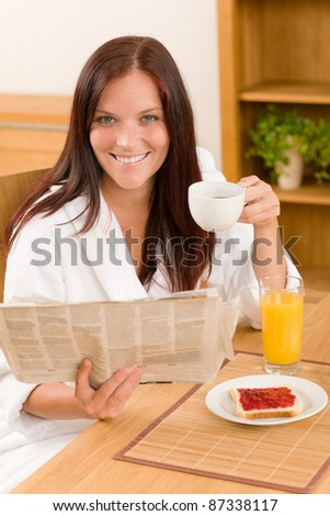Breakfast coffee and toast happy woman read newspapers at home