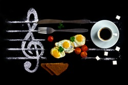 Breakfast concept as notes in music. Fried eggs with tomatoes on a background of a treble clef with a cup of coffee