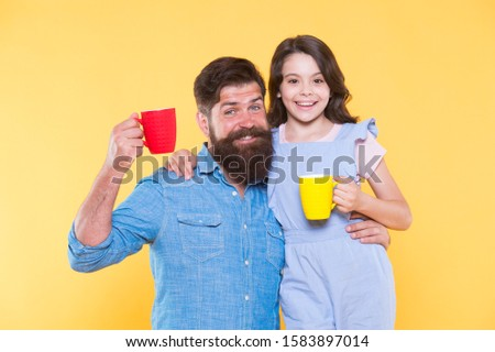 Breakfast concept. Good morning. Having coffee together. Healthy lifestyle. Family drinking tea. Bearded man and happy girl holding mugs. Father and daughter hot drink. Drink water. Drink fresh juice.