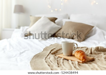 Stock Photo breakfast, coziness, morning, holidays and winter concept - cozy bedroom with coffee cup and croissant on wooden board in bed at home