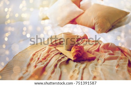 breakfast, coziness, morning, holidays and winter concept - cozy bedroom with coffee cup and croissant on wooden board in bed at home #751391587