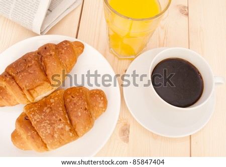 Breakfast - Croissants, Coffee, Orange Juice and Newspapers on Wooden Table