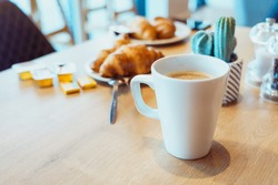 Breakfast, cup of coffee and fresh croissants on a table in a hotel cafe. Selective focus, copy space