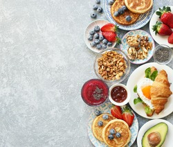 Breakfast food table. Festive brunch set, meal variety with granola, fried egg, pancakes, croissants, smoothie ,fresh vegetables, berries and fruits. Overhead view, copy space