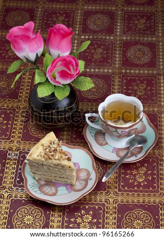 Breakfast in a retro style. Cake, tea with lemon and a bouquet in a porcelain dish.