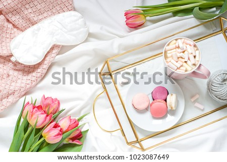 Breakfast in bed pastel flat lay composition with flowers, a cup o coffee  and sweets. Concept woman's or mother's day top view