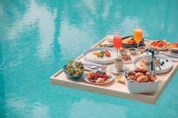 Breakfast in swimming pool, floating breakfast in tropical resort. Table relaxing in calm pool water, healthy breakfast and fruit plate by resort pool. Exotic summer diet. Tropical beach lifestyle