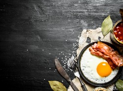 Breakfast in the morning. Beans with fried egg and bacon. On a black wooden background.