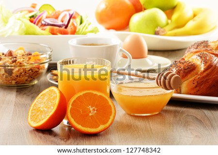 Breakfast including coffee bread honey orange juice muesli and fruits