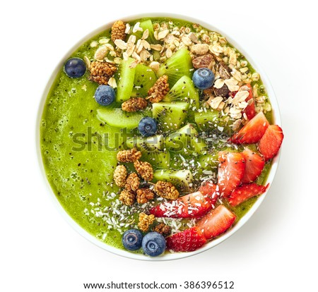 breakfast kiwi smoothie bowl topped with oat flakes and berries isolated on white background, top view