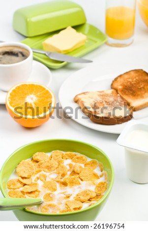 breakfast meal - bowl of cornflakes with milk, two buttered toasts, half of an orange, orange juice and coffee
