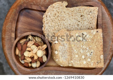 Breakfast meal in the very first of direct morning sunlight, including whole wheat breads, almond nuts, peanuts, groundnuts, cashew nut, and macadamia on the wooden food tray and over round table.